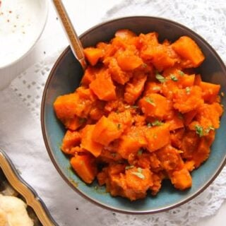 braised pumpkin with spices in a blue bowl with yogurt