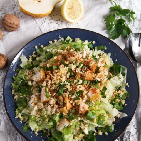 salad leaves, celeriac, pears and walnuts on a blue plate