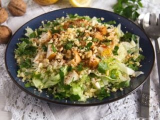 large plate full of salad leaves and chopped walnuts