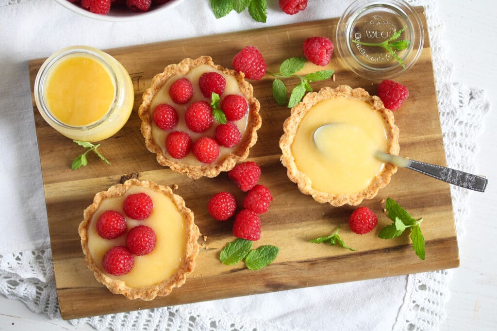 fresh raspberry tarts with lemon being assembled on a wooden board