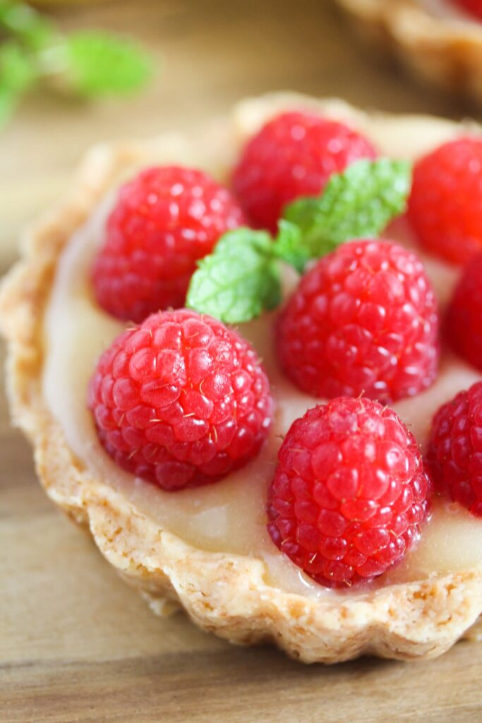 one tart with lemon filling and jewel like raspberries on top
