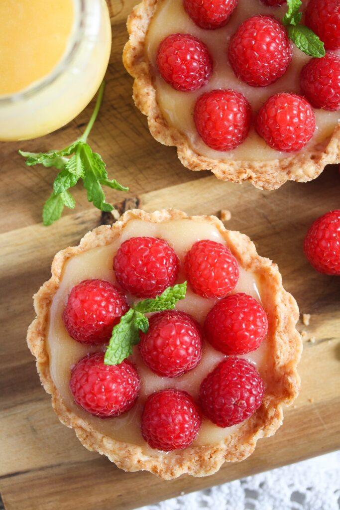 two lemon curd raspberry tarts on a wooden board