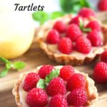 small cakes topped with raspberries on a cutting board