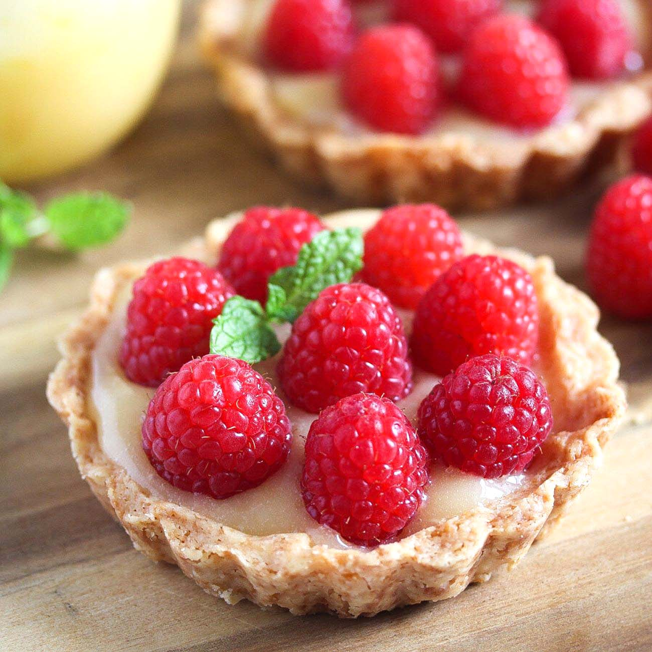 lemon curd tartlets with fresh raspberries on a cutting board
