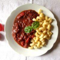 vegan seitan stew with pasta on a white plate