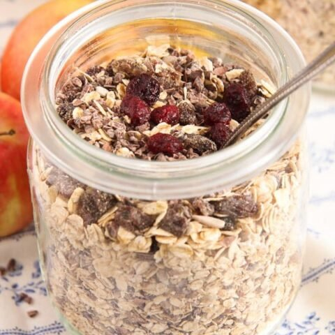 homemade muesli mix in a large jars with bananas behind