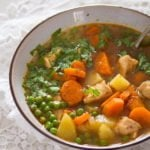homemade chicken and potato soup with peas and carrots in a bowl