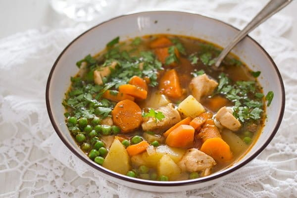 bowl of chicken and potato soup sprinkled with parsley