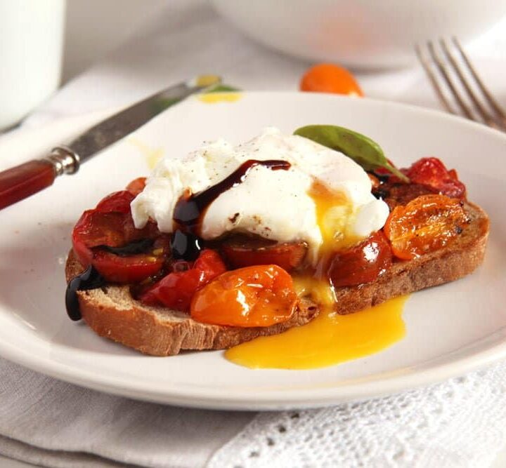 runny poached egg on sourdough with tomatoes