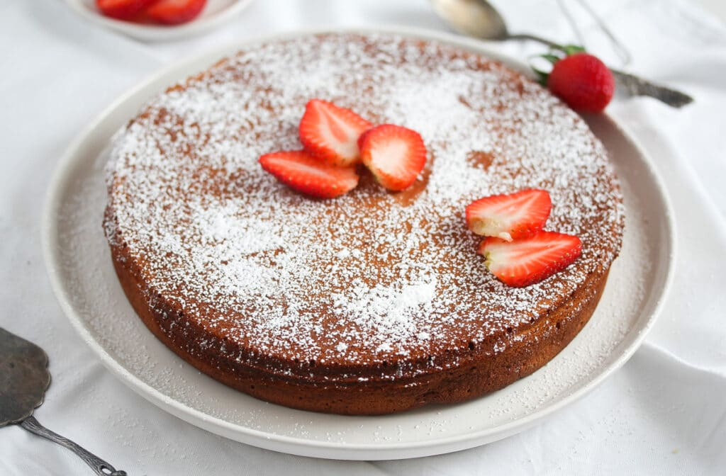 round flat moist cake on a serving platter decorated with strawberries