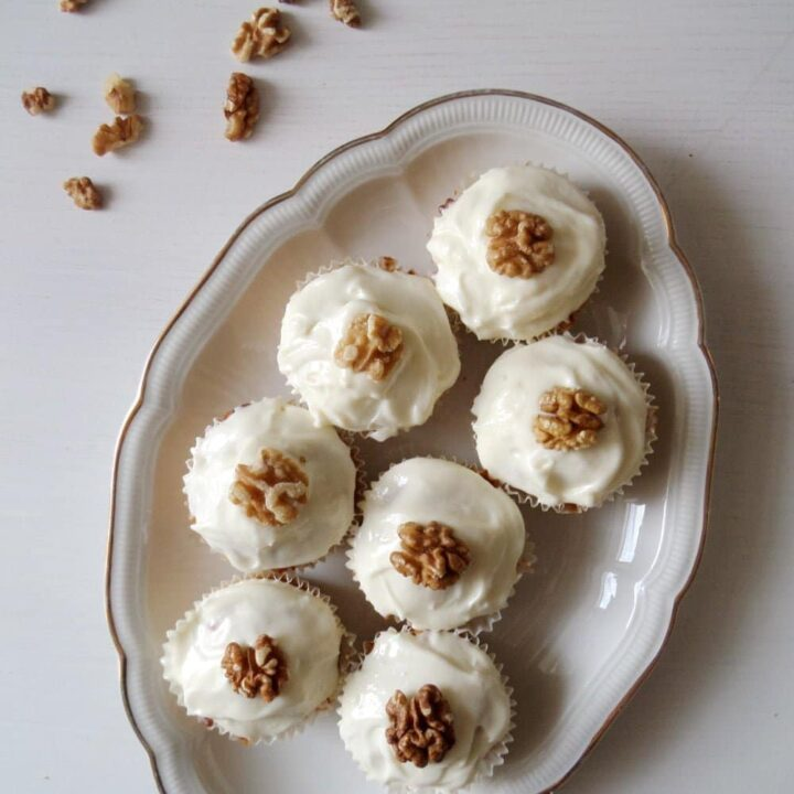 seven carrot cupcakes topped with frosting and walnuts on a vintage platter.
