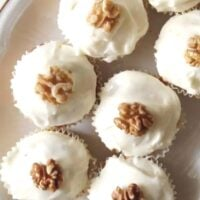 carrot cake muffins frosted and decorated with walnuts close up.