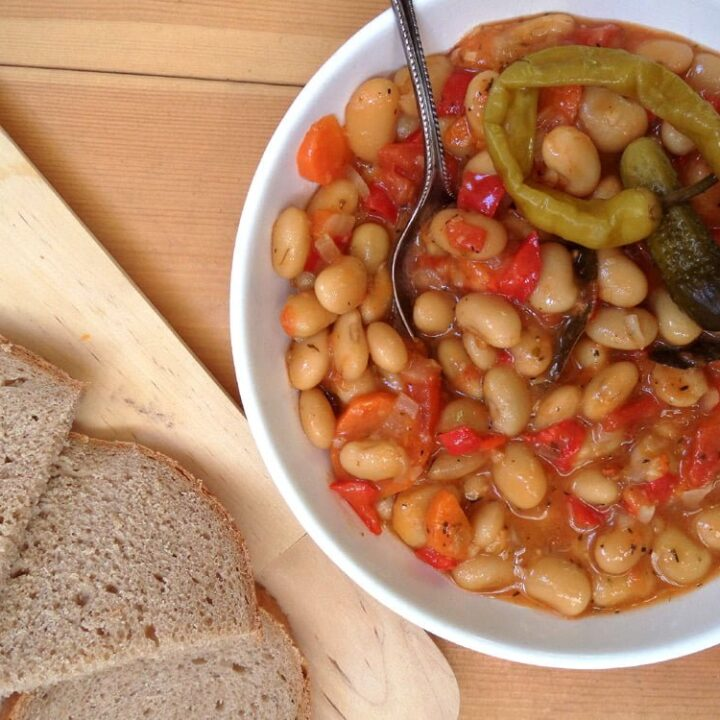 bowl of white bean stew served with bread and gherkins on a kitchen cloth