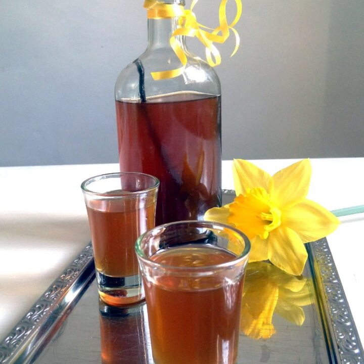 bottle and glasses with honey liqueur on a silver tray
