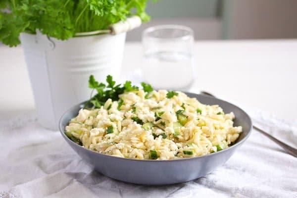 orzo lemon salad on a table with fresh herbs behind