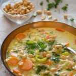 bowl of african peanut soup with a small bowl of roasted peanuts behind it.