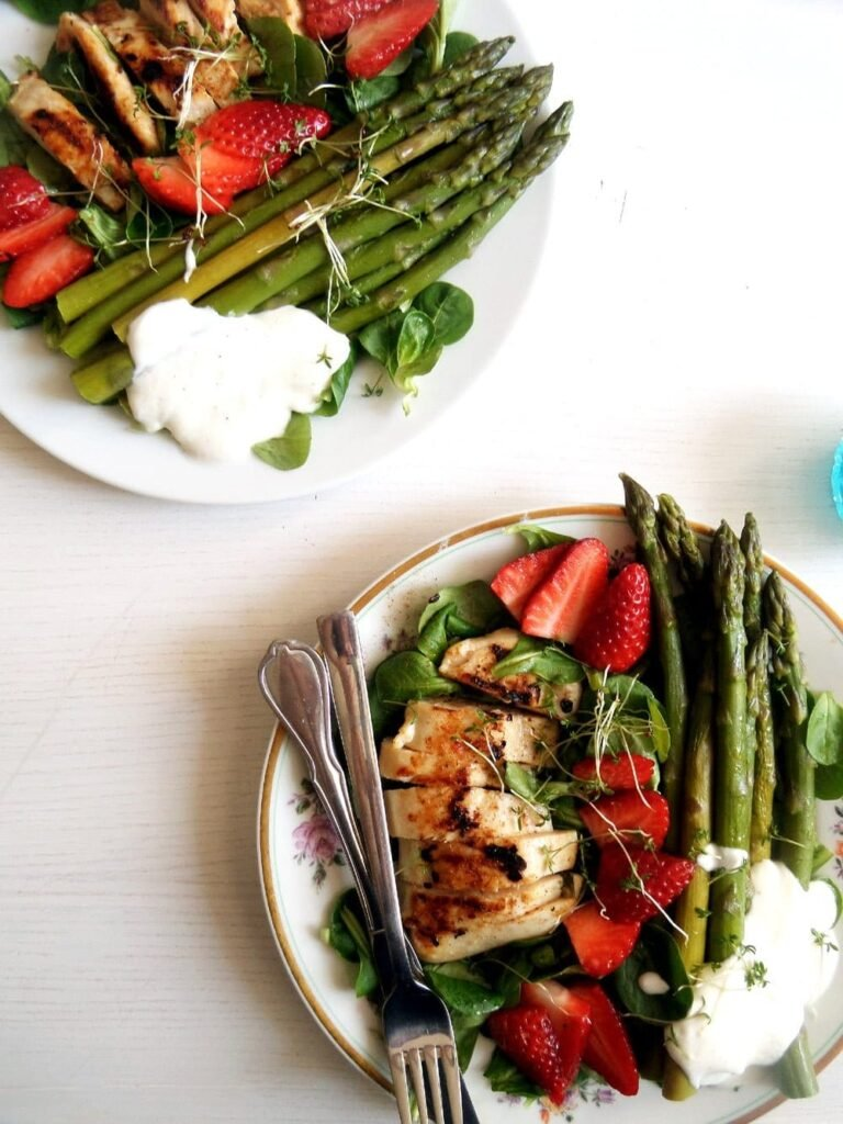 two plates with spring salad with chicken, asparagus and strawberries