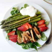 asparagus strawberry salad with chicken on a white plate