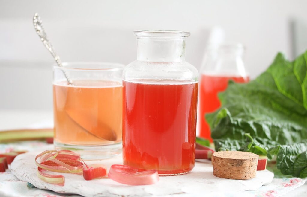 rhubarb peel syrup on the table with leaves behind