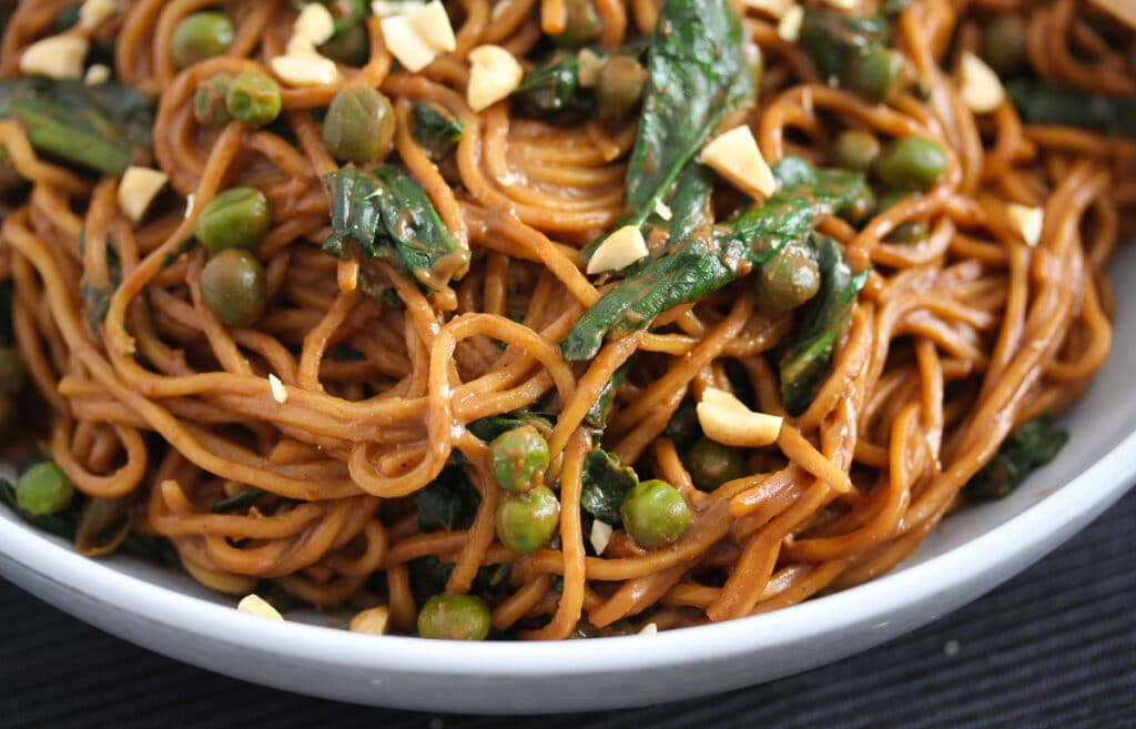 close up of brown colored noodles with peanuts on top