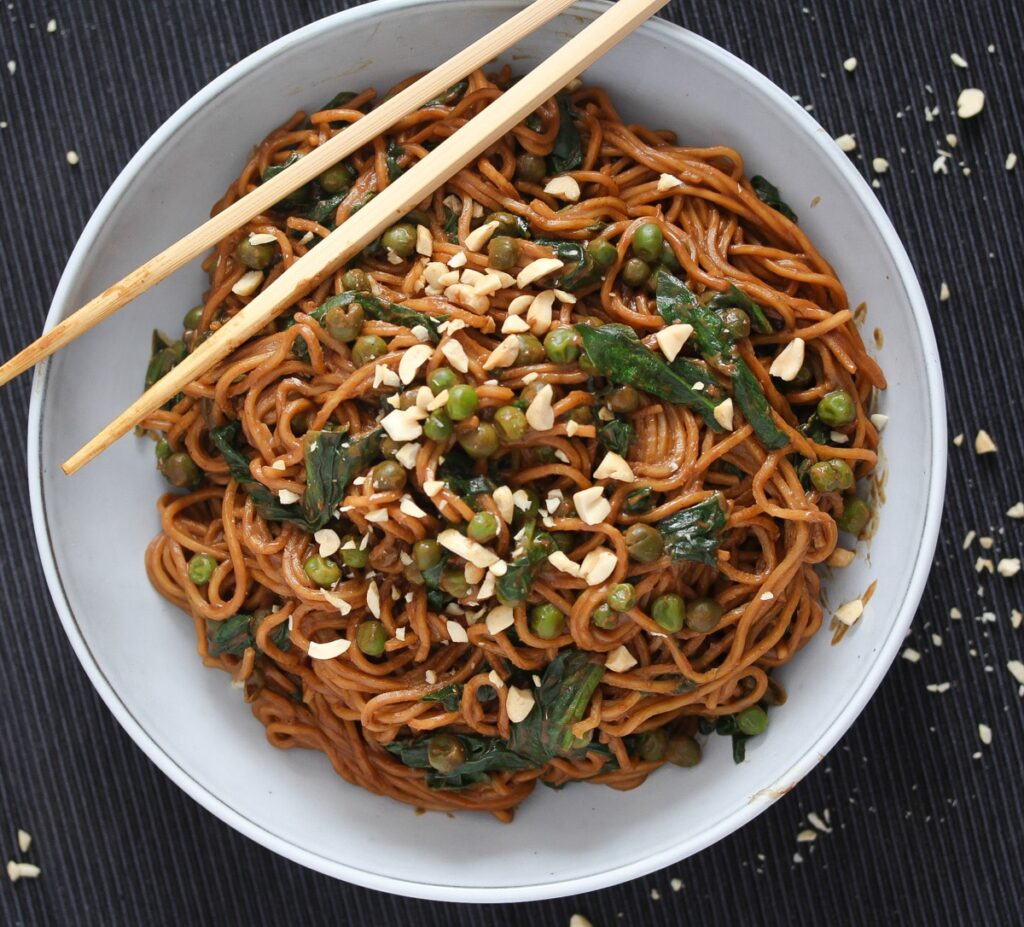 bowl of chinese noodles with brown sauce and spinach