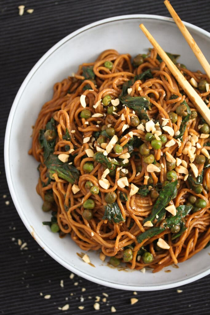spinach peanut butter pasta in a bowl on a black table