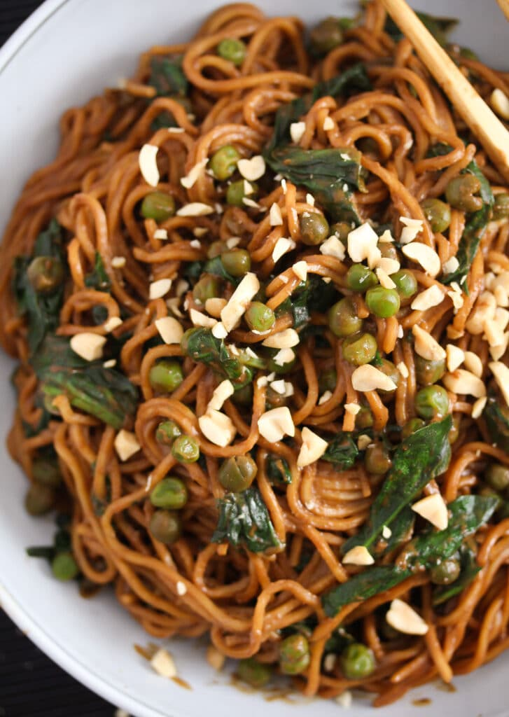 peanut butter noodles with spinach and peas close up
