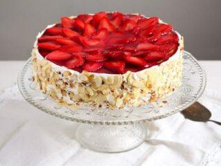 strawberry yogurt cheesecake on a cake platter