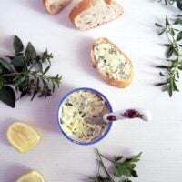 small pot with garlic butter, bread slices, herbs and lemon on the table.