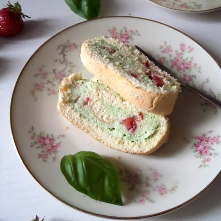 sliced strawberry basil roulade on a plate with basil leaves