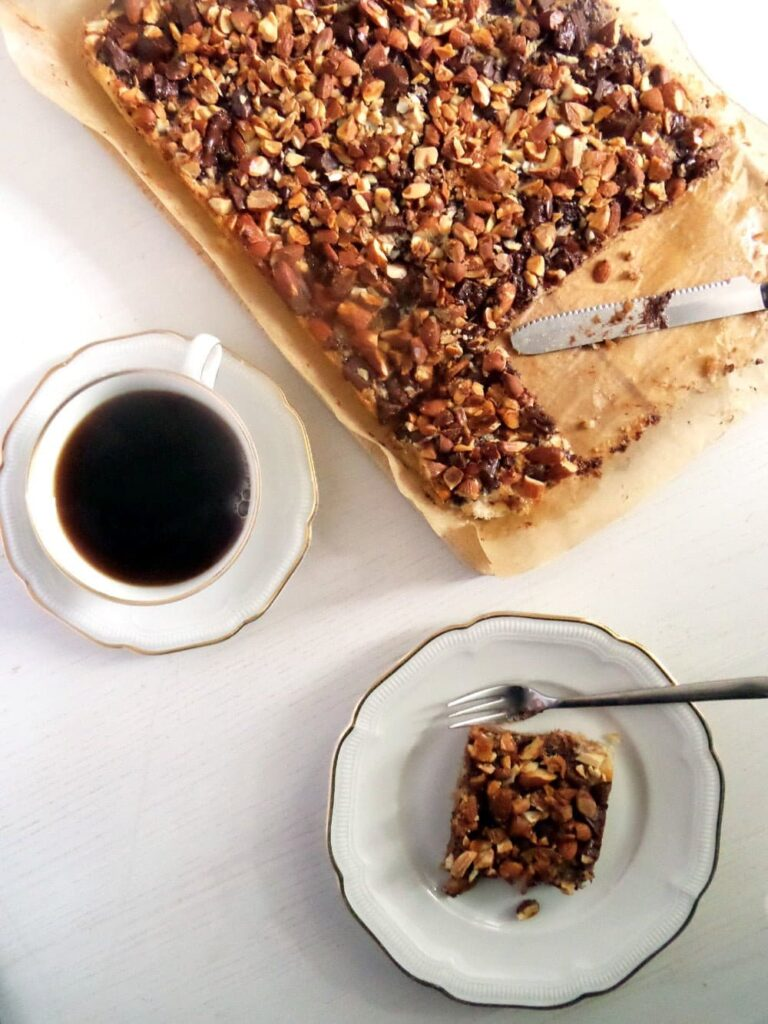 biscuit cake with nuts and chocolate and a cup of coffee