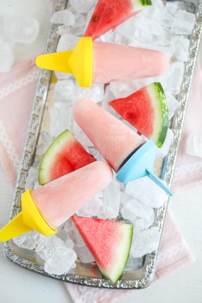 three watermelon ice lollies on a tray with ice cubes