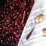 roasted cherries in a roasting tin with a cinnamon stick