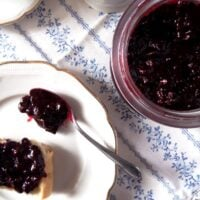 black currant jam in a jar and on a slice of bread