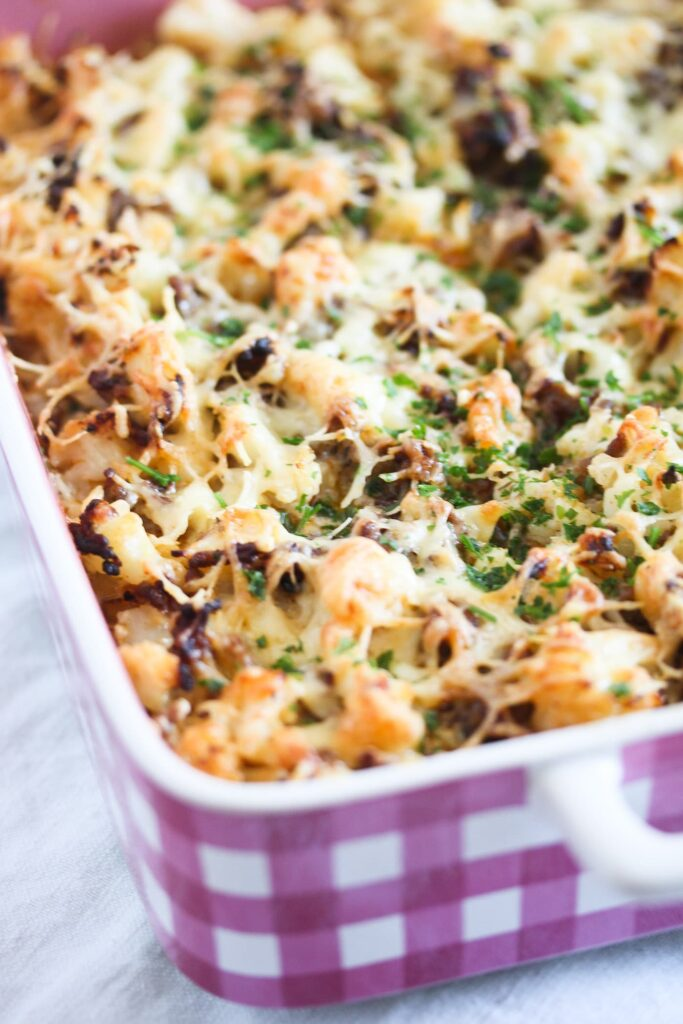 beef bake with cauliflower and cheese in a pink baking dish