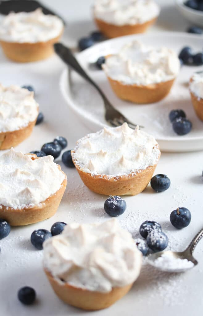 mini blueberry tarts with meringue topping on the table