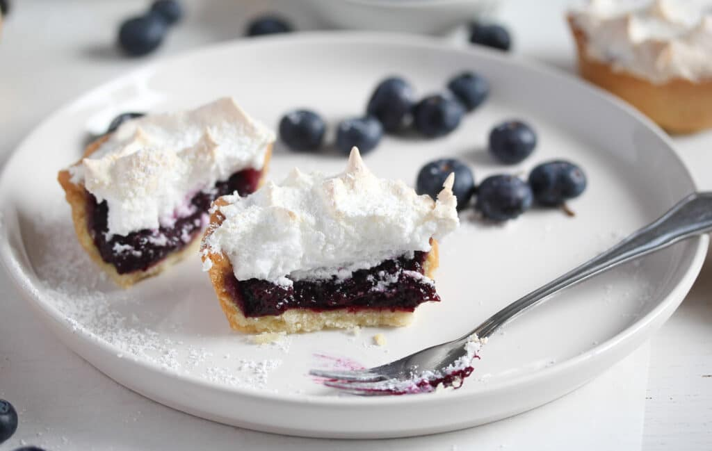 cut blueberry mini tart with blueberry curd in the middle
