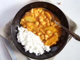 black bowl with apple curry and rice.