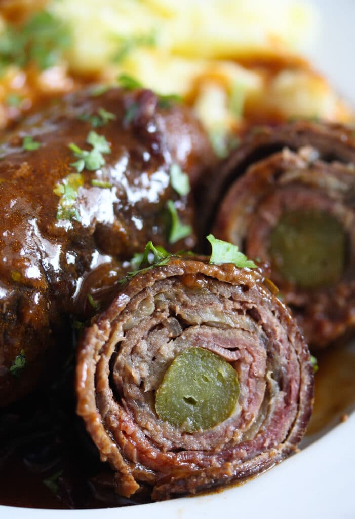 close up of a sliced beef roulade with gherkin inside