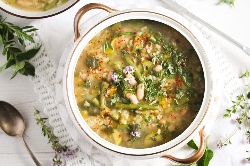 bean soup with vegetables in a white pot