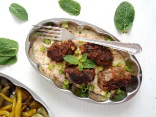 turkish meat rolls with yogurt sauce on a plate