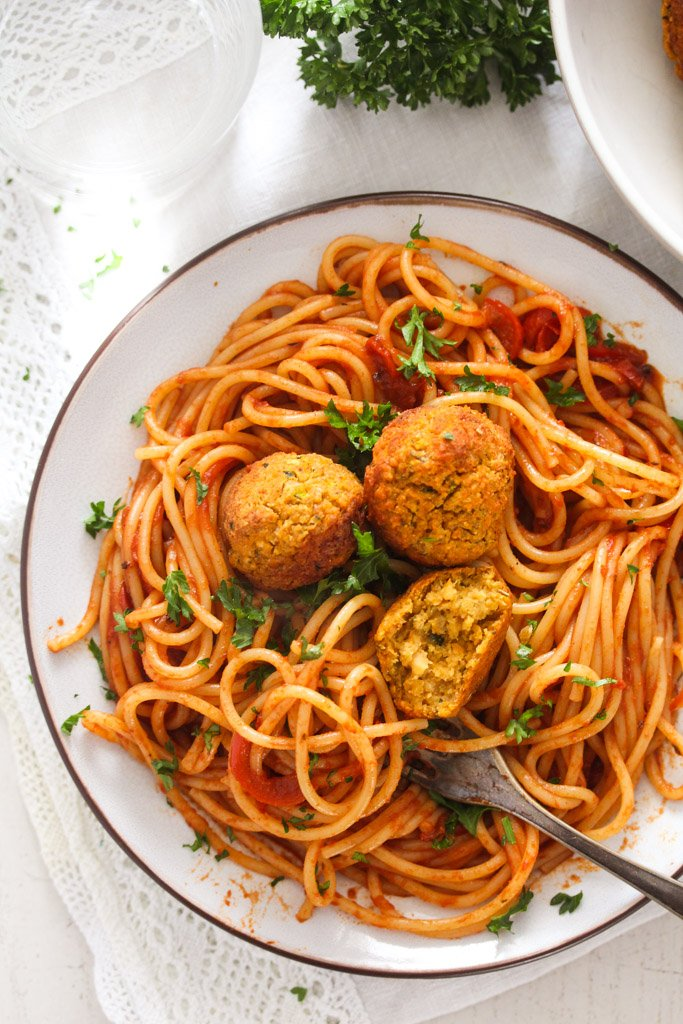 tangled spaghetti with red pepper sauce and chickpea balls on a plate.