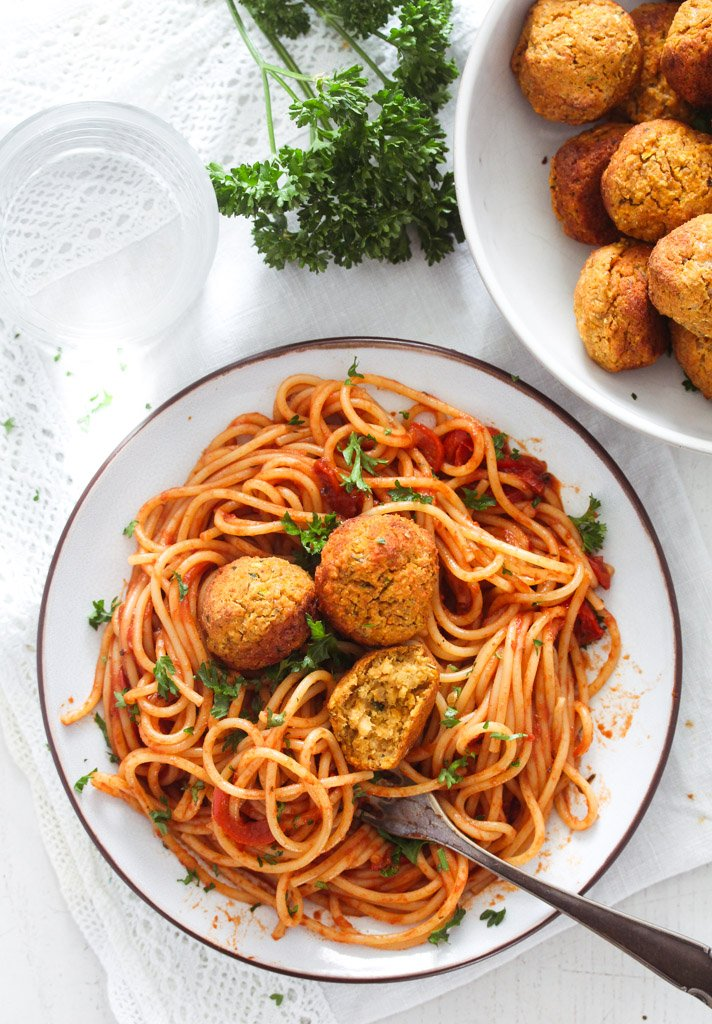overhead view of a plate with lots of spaghetti with tomato sauce topped with vegetarian balls.
