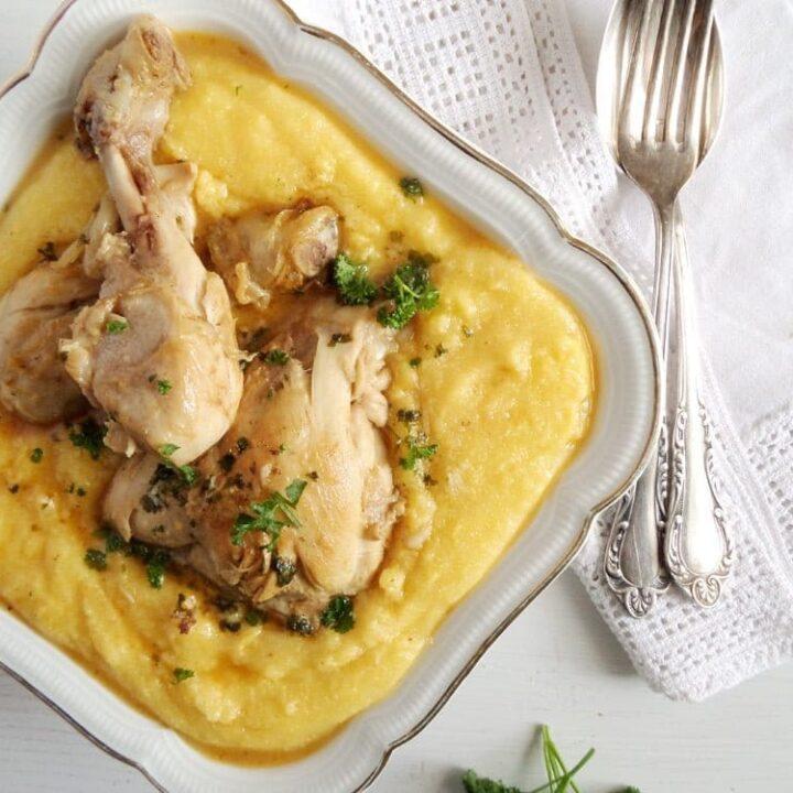 garlic chicken legs with polenta in a serving bowl