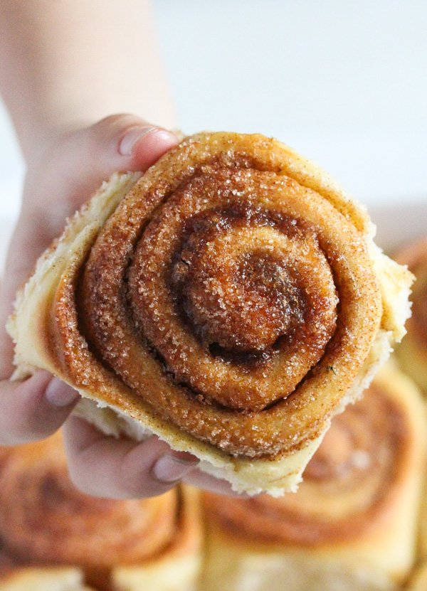 girl holding one sweet roll with cinnamon