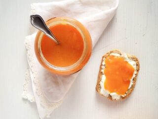orange jam in a jar and on bread