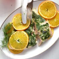 salmon with white wine sauce served with orange slices