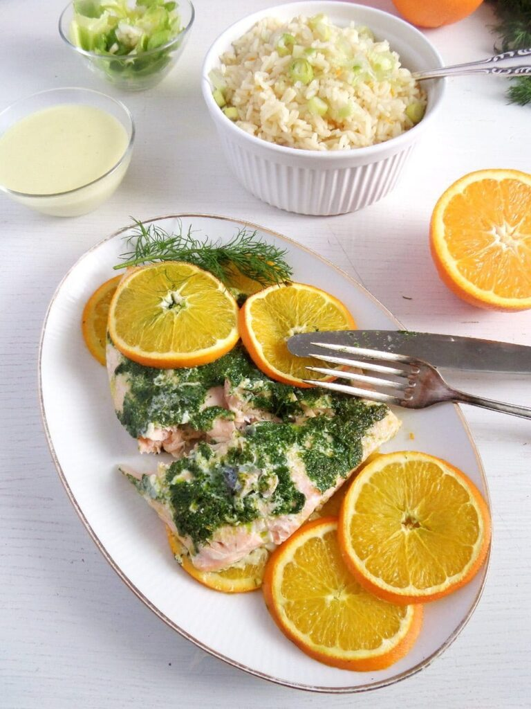 orange dill salmon served with orange slices on a large plate
