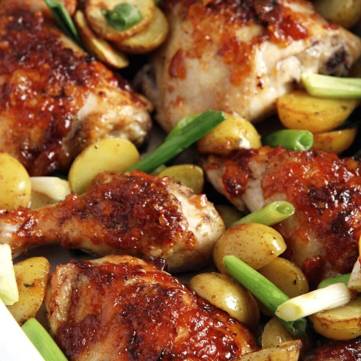 baked mango chicken with potatoes and green onions on a tray