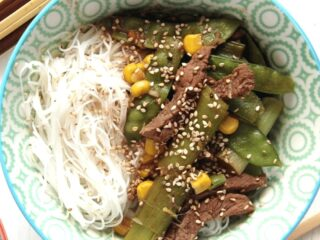 rice noodle bowl with ginger and green onions beef.
